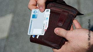 Foto Hände, die die UCCard aus dem Portemonnaie ziehen