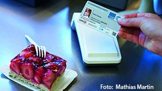 Foto: Jemand hält die UCCard in der Hand und vor ihm oder ihr steht ein Stück Erdbeerkuchen
